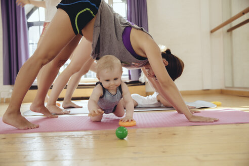 Two mothers working out on yoga mats with babies playing around them - MFF04008
