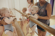 Two mothers holding up their small children to barre in dance studio - MFF04014
