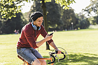 Laughing man on racing cycle looking at cell phone in a park - UUF11743
