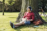 Man using laptop and headphones in park - UUF11749