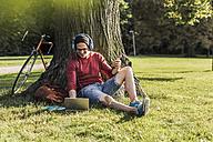 Man using laptop in park - UUF11752