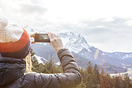 Germany, Bavaria, Zugspitze, back view of woman taking picture with smartphone - MMAF00145