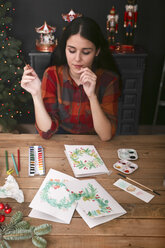 Young woman painting Christmas card with water colors - RTBF01018