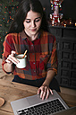 Smiling woman with cup of coffee using laptop at Christmas time - RTBF01021