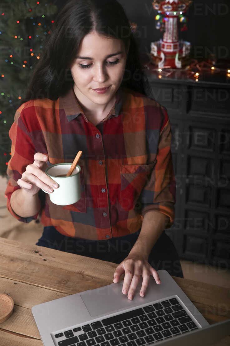 Smiling woman with cup of coffee using laptop at Christmas time - RTBF01021 - Retales Botijero/Westend61