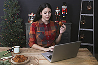 Young woman using laptop while eating croissant at Christmas time - RTBF01024