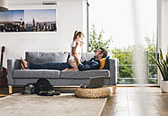 Father playing with his daughter on couch - UUF11780