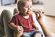 Mother and son at home eating ice lolly - UUF11786