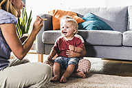 Mother feeding kids in living room - UUF11792