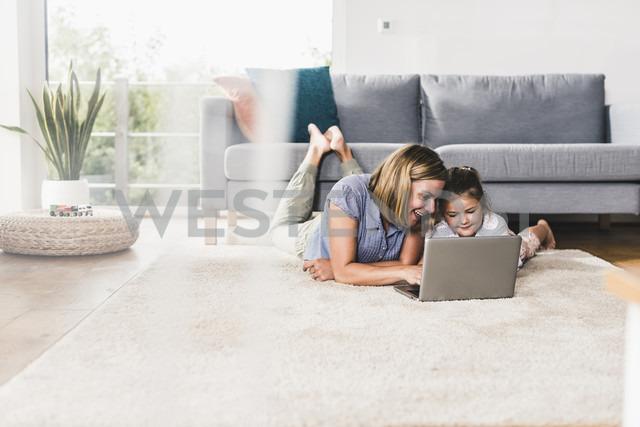 Mother and daughter using laptop, lying on carpet - UUF11798 - Uwe Umstätter/Westend61