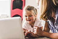 Mother and daughter having fun, using laptop - UUF11801