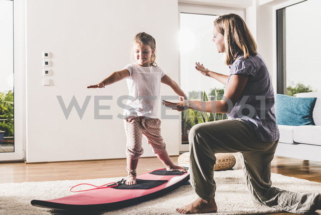 Mother and daughter exercising with surfboard in living room - UUF11804 - Uwe Umstätter/Westend61