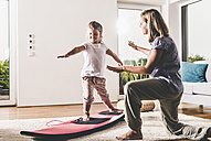 Mother and daughter exercising with surfboard in living room - UUF11804