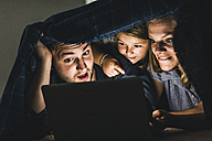 Happy family hiding under blanket, watching film on laptop - UUF11822