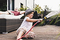 Little girl playing with garden hose - UUF11828