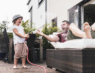 Fathercand daughter in the garden, daughter splashing water with hose - UUF11831