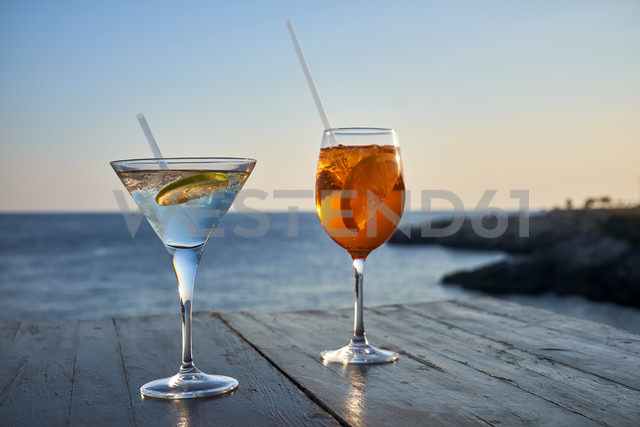 Glass of ice-cooled Spritz with orange slice and glass of Martini with lime slice in front of the sea - DIKF00270 - Dirk Kittelberger/Westend61