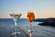 Glass of ice-cooled Spritz with orange slice and glass of Martini with lime slice in front of the sea - DIKF00270