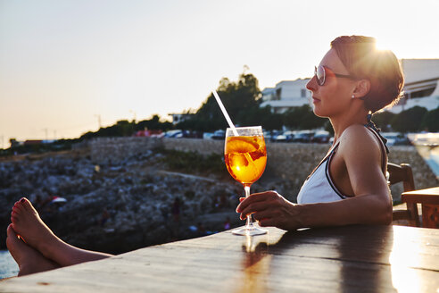 Italy, Santa Caterina, woman relaxing on promenade with glass of Spritz at sunset - DIKF00273