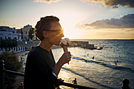 Italy, Santa Maria al Bagno, woman eating ice cream cone at backlight - DIKF00276