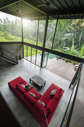Modern minimalist living room with red couch in contemporary design house with glass facade surrounded by lush tropical garden with pool - SBOF00798