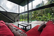 Modern minimalist living room with red couch in contemporary design house with glass facade surrounded by lush tropical garden with pool - SBOF00804