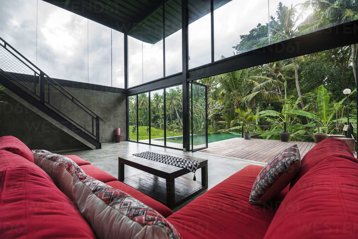 Modern minimalist living room with red couch in contemporary design house with glass facade surrounded by lush tropical garden with pool - SBOF00804 - Steve Brookland/Westend61