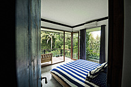 Modern cozy bedroom in contemporary design house with glass facade surrounded by lush tropical garden - SBOF00807