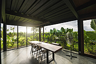 Modern wooden table in contemporary design house with glass facade surrounded by lush tropical garden - SBOF00810