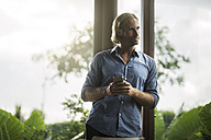 Handsome man holding smartphone in contemporary design house with glass facade surrounded by lush tropical garden - SBOF00813