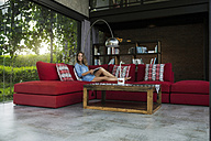 Woman with book relaxing on red couch in modern living room with glass facade - SBOF00819