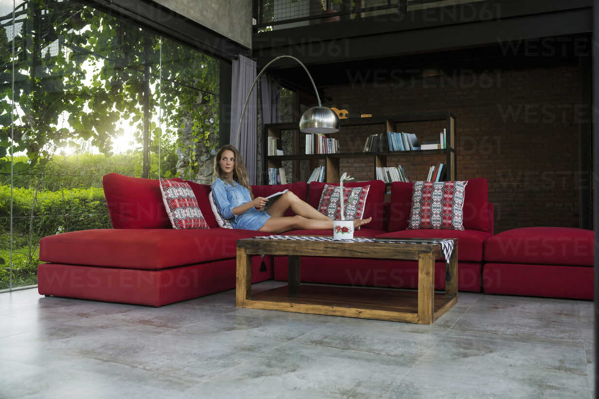 Woman with book relaxing on red couch in modern living room with glass facade - SBOF00819 - Steve Brookland/Westend61