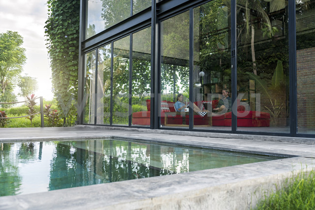 Garden view through glass facade of couple with laptop and book relaxing on red couch in modern design house in front of swimming pool - SBOF00822 - Steve Brookland/Westend61