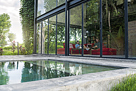 Garden view through glass facade of couple with laptop and book relaxing on red couch in modern design house in front of swimming pool - SBOF00822