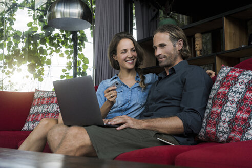 Woman with credit card smiling at husband looking at laptop on a red couch in a modern living room - SBOF00825