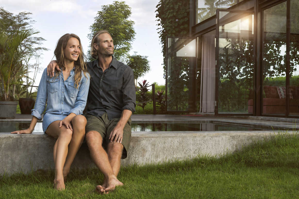 Smiling hugging couple sitting on the edge of a pool in front of their design house - SBOF00828 - Steve Brookland/Westend61