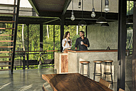 Couple having breakfast and smiling at each other in modern design kitchen with glass facade surrounded by lush tropical garden - SBOF00831