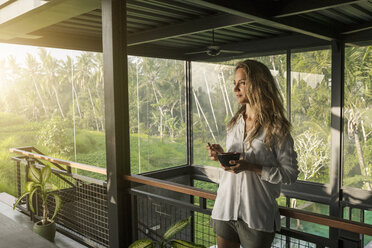Smiling woman eating cereal in contemporary design house with pool and glass facade surrounded by lush tropical garden - SBOF00834