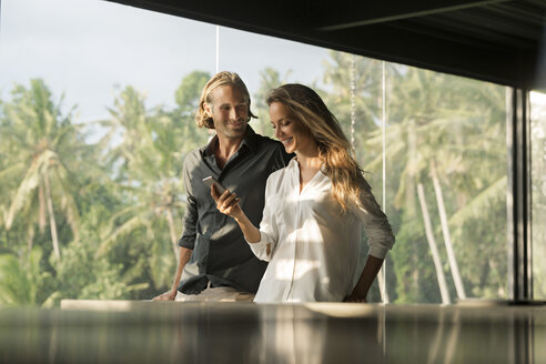 Smiling couple with smartphone in design house - SBOF00837