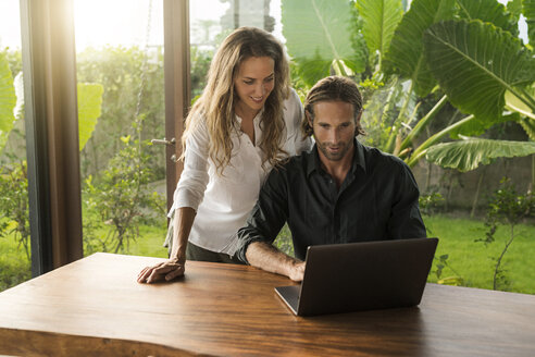 Smiling couple looking at laptop in design house surrounded by lush tropical garden - SBOF00840