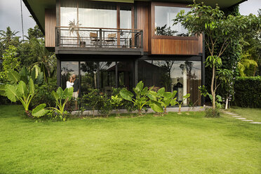 Garden view of couple standing in modern design house surrounded by lush tropical garden - SBOF00843