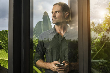 Handsome man standing behind glass facade of design house holding smartphone surrounded by lush tropical garden - SBOF00846