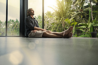 Handsome man sitting on floor and leaning on glass facade with stunning tropical garden in background - SBOF00852