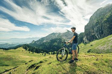 Germany, Bavaria, Pfronten, young man with mountain bike on alpine meadow near Aggenstein - PNPF00020