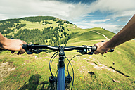 Germany, Bavaria, Pfronten, mountainbiker riding downhill on alpine meadow near Aggenstein - PNPF00023