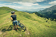 Germany, Bavaria, Pfronten, woman with mountain bike on alpine meadow near Aggenstein - PNPF00026