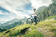 Germany, Bavaria, Pfronten, smiling teenage girl with mountain bike on alpine meadow near Aggenstein - PNPF00029