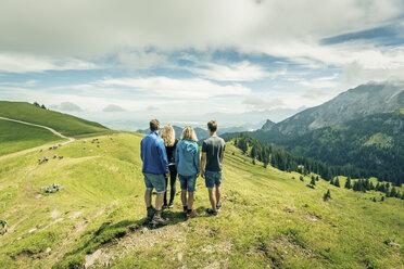 Germany, Bavaria, Pfronten, family enjoying the view on alpine meadow near Aggenstein - PNPF00032