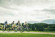 Germany, Bavaria, Pfronten, family riding mountain bikes at ladeside - PNPF00035