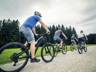 Germany, Bavaria, Pfronten, family riding mountain bikes in the countryside - PNPF00041